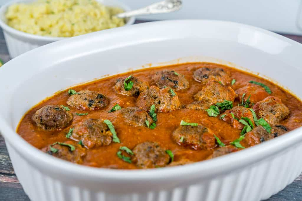A casserole dish with Moroccan Meatballs in a spiced flavorful tomato sauce | Babaganosh.org