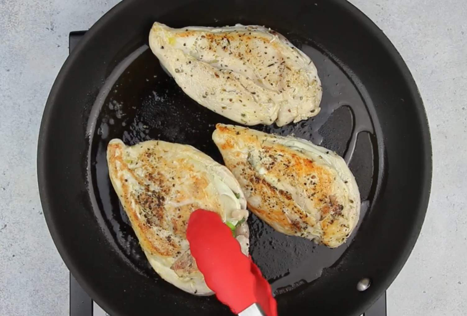 image of stuffed chicken breast cooking in skillet
