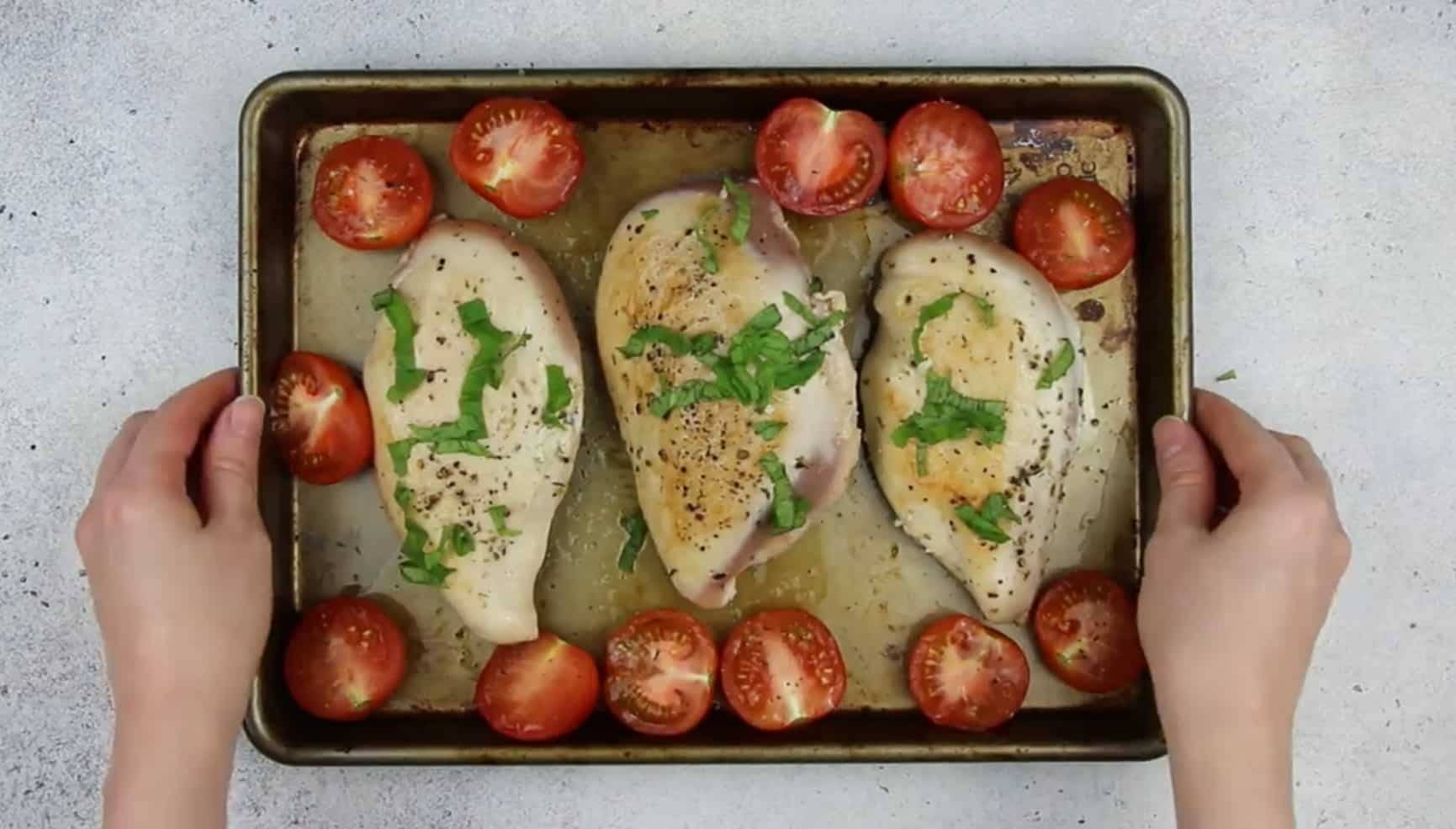 image of stuffed chicken breast and tomatoes on a baking pan