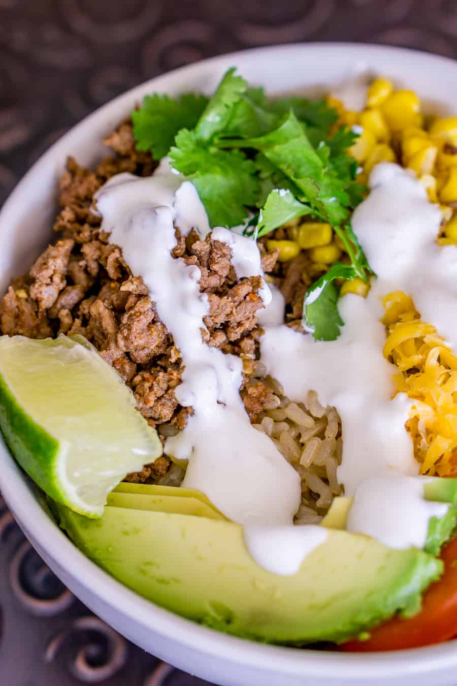 image of brown rice taco bowl with lime crema drizzle