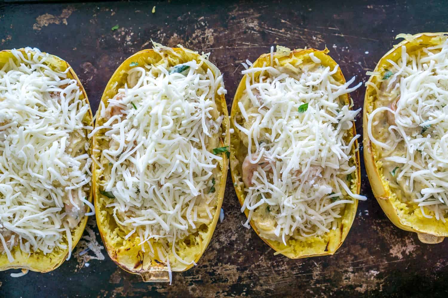 image of roasted spaghetti squash stuffed with shrimp topped with shredded cheese