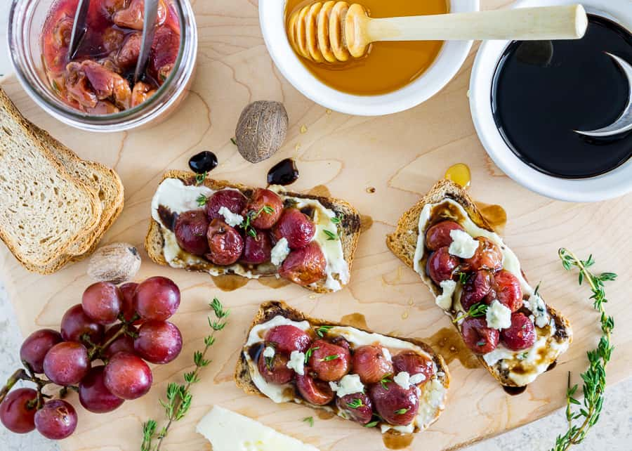 overhead shot of roasted grape crostini with blue cheese spread