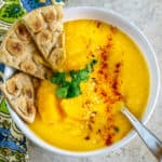bowl of lentil butternut squash soup with garlic pita wedges