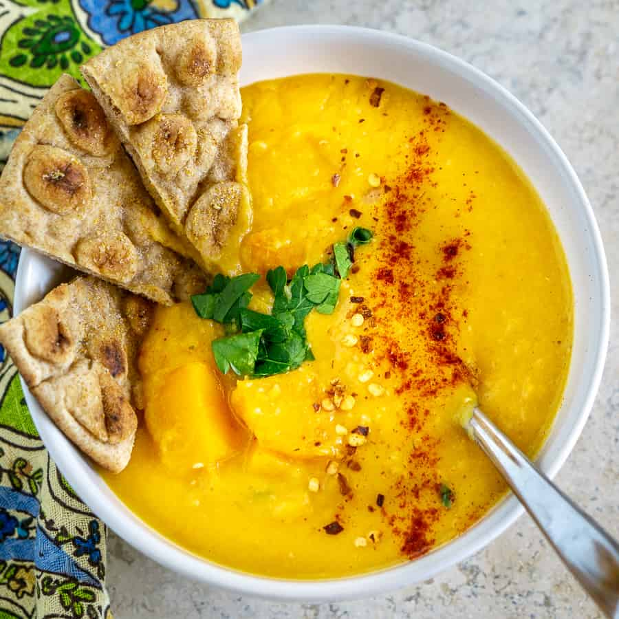 bowl of lentil butternut squash soup with garlic pita wedges