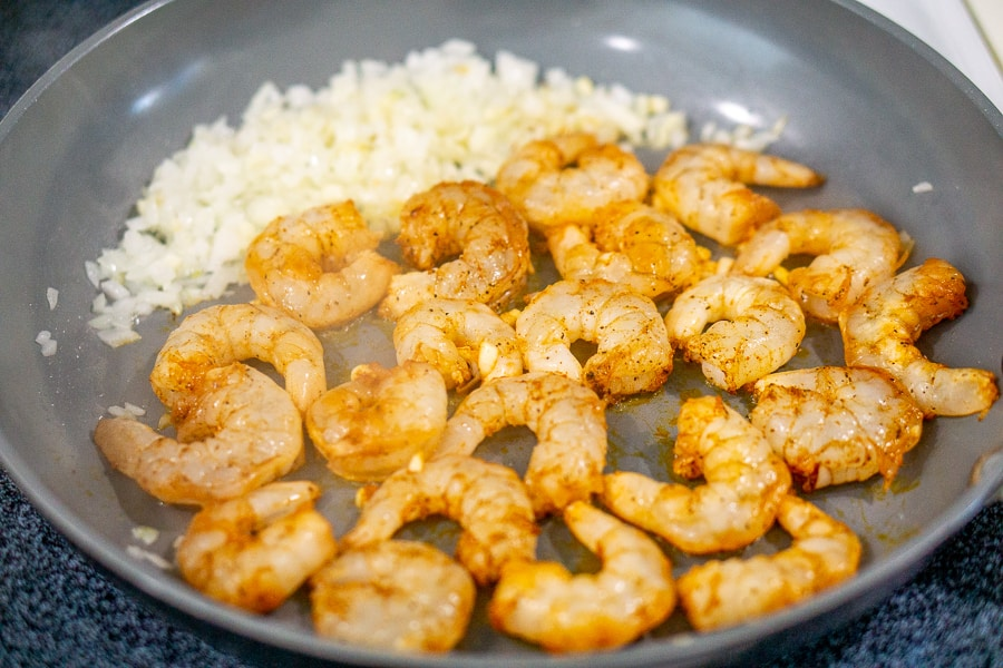 shrimp cooking in a skillet with onions