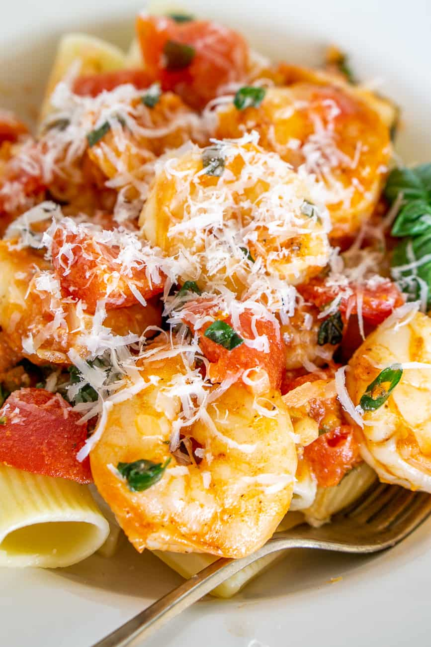 close up of shrimp in tomato sauce over pasta sprinkled with Parmesan