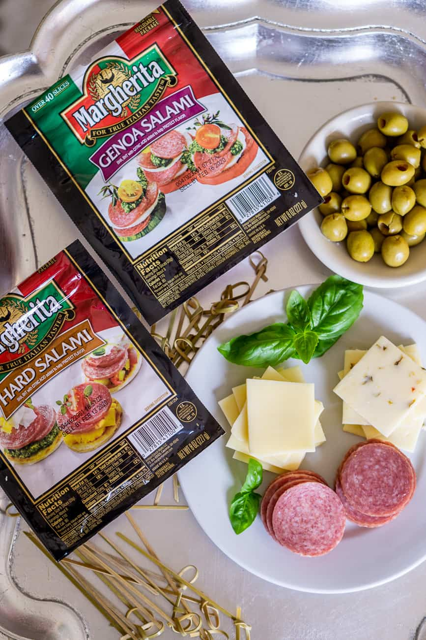 ingredients to make an easy salami appetizer: salami, olive, cheese on a tray