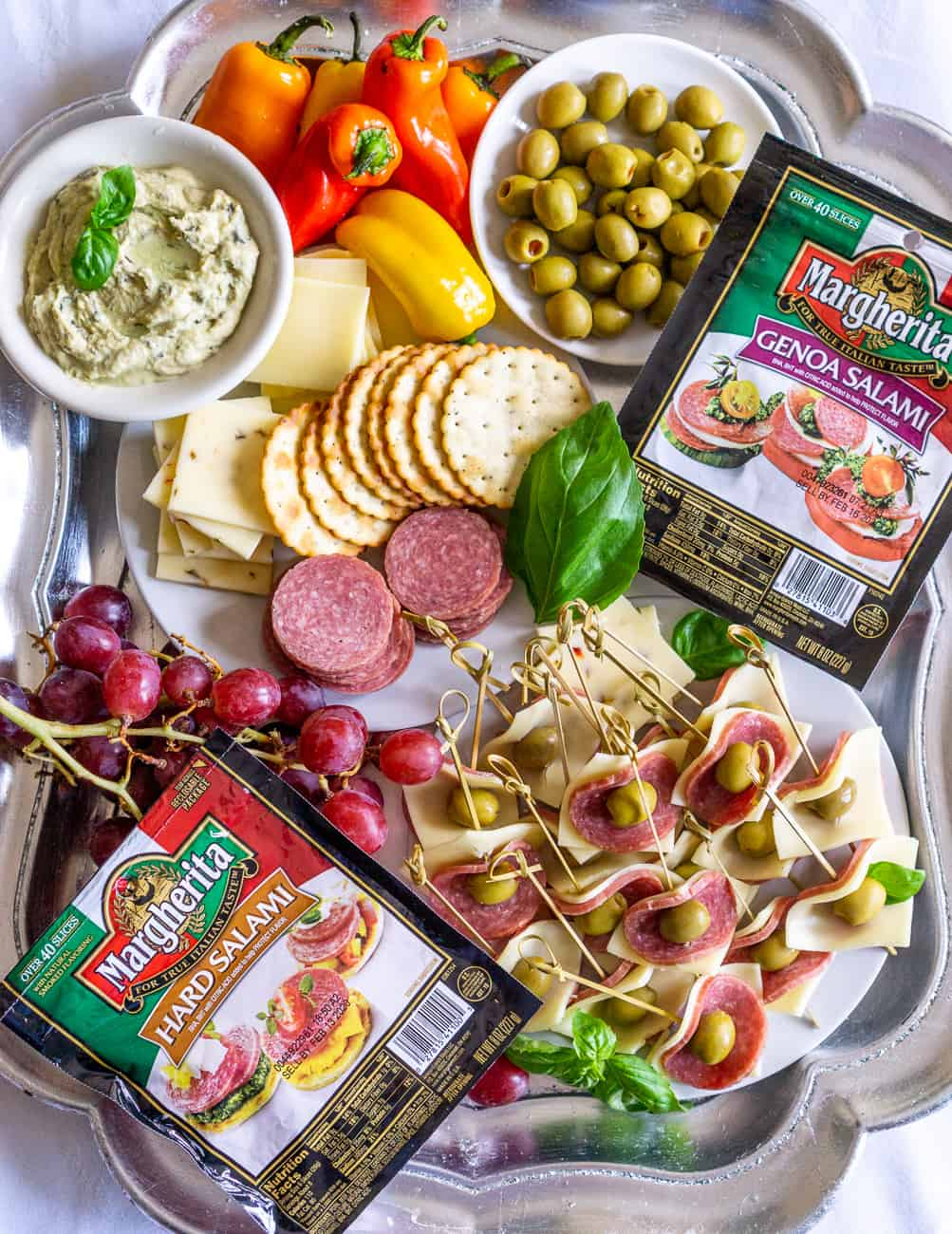 appetizer tray with a plate of salami appetizers, hummus, crackers, salami, cheese, grapes