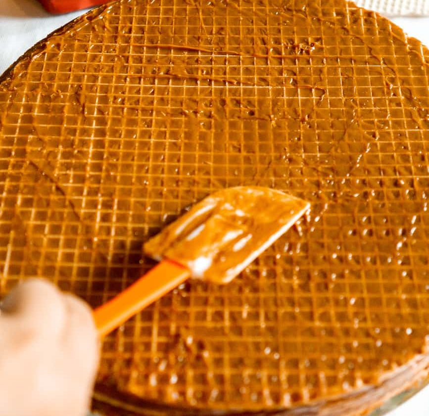 spreading dulce de leche on wafers with a spatula