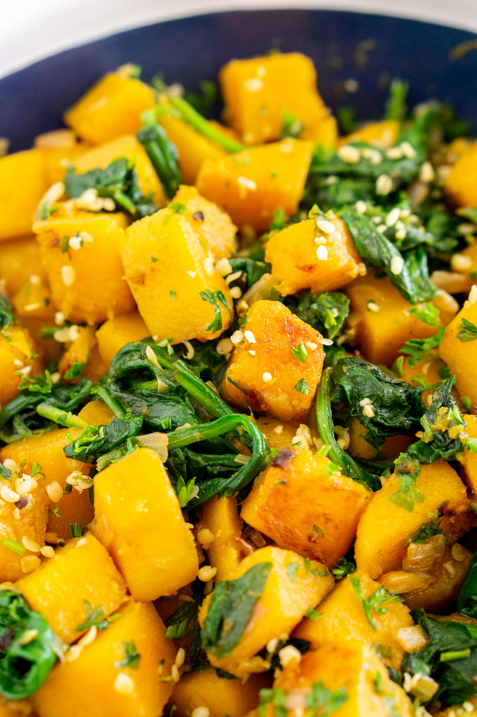 close up of cubed pan-fried butternut squash with spinach
