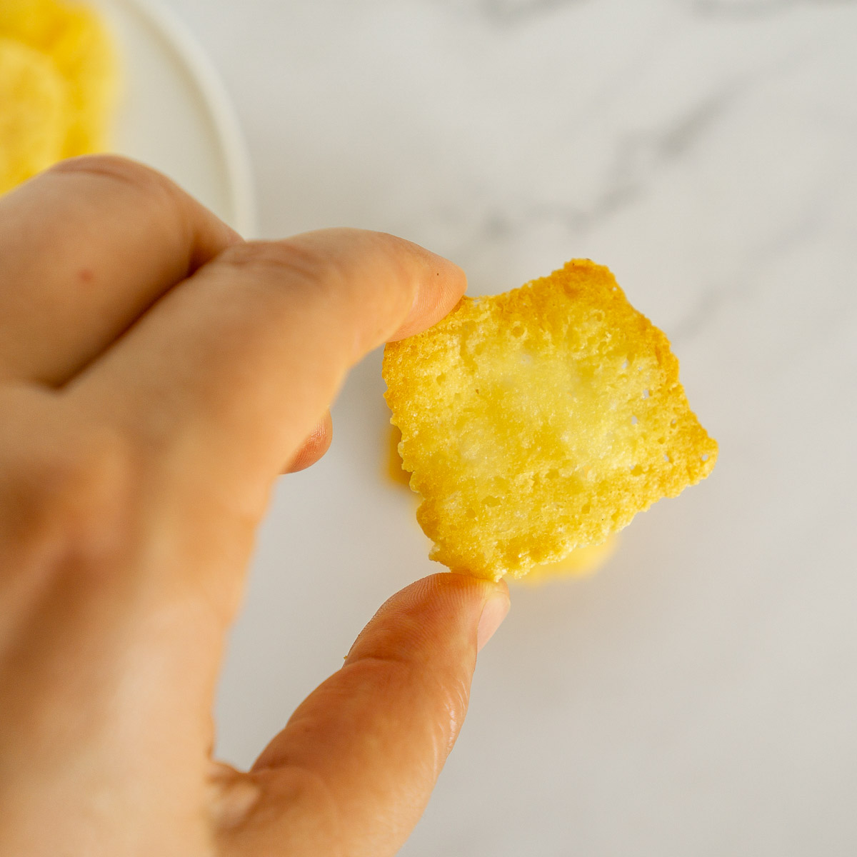 hand holding asiago cheese crisp