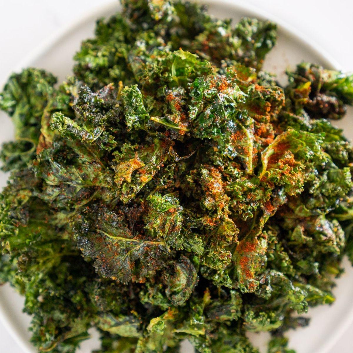 Plate of crispy kale chips seasoned with Cajun spice.