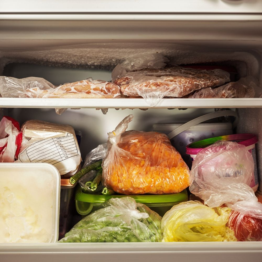 freezer filled with leftovers and frozen meat to save money