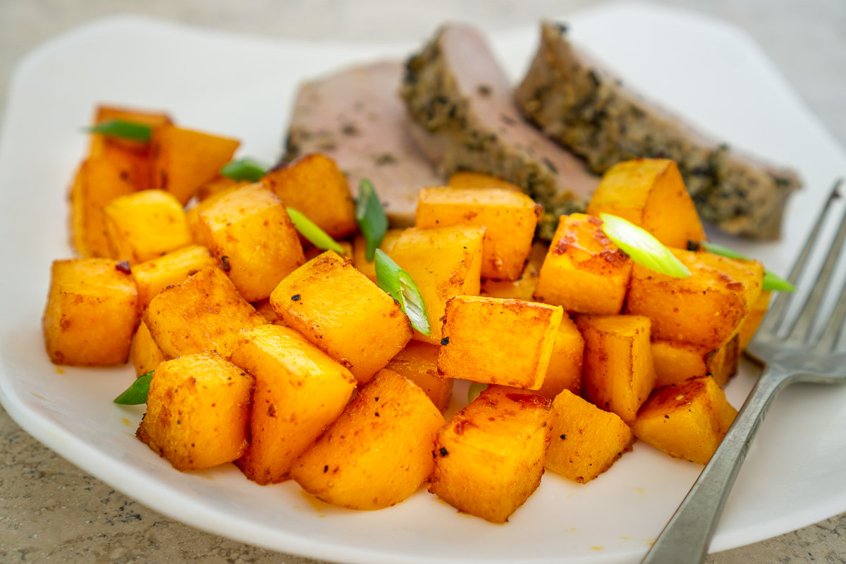 gochujang roasted butternut squash on a plate with pork chops