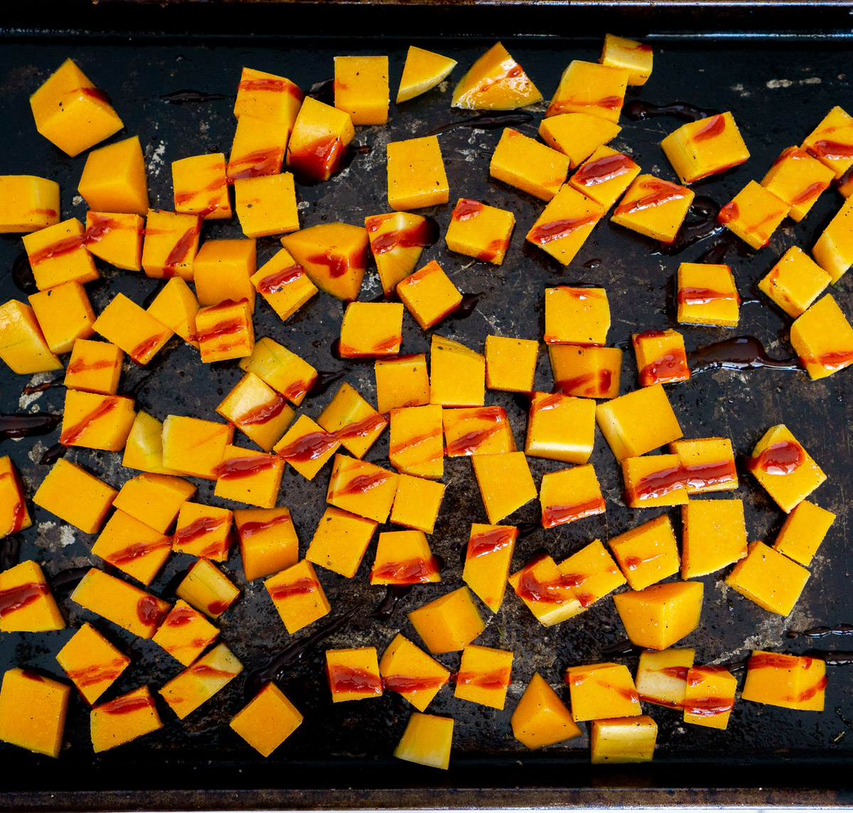 cubed butternut squash with gochujang sauce drizzled
