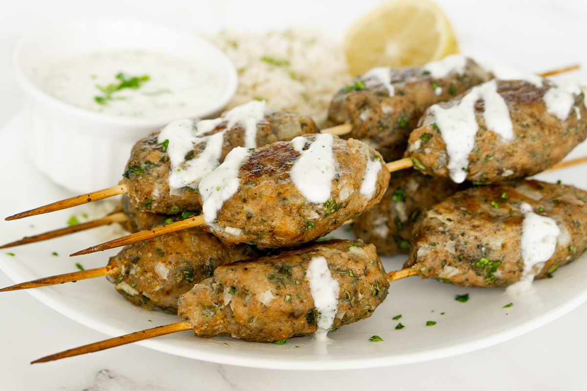 chicken kofta kebabs with yogurt sauce on a plate