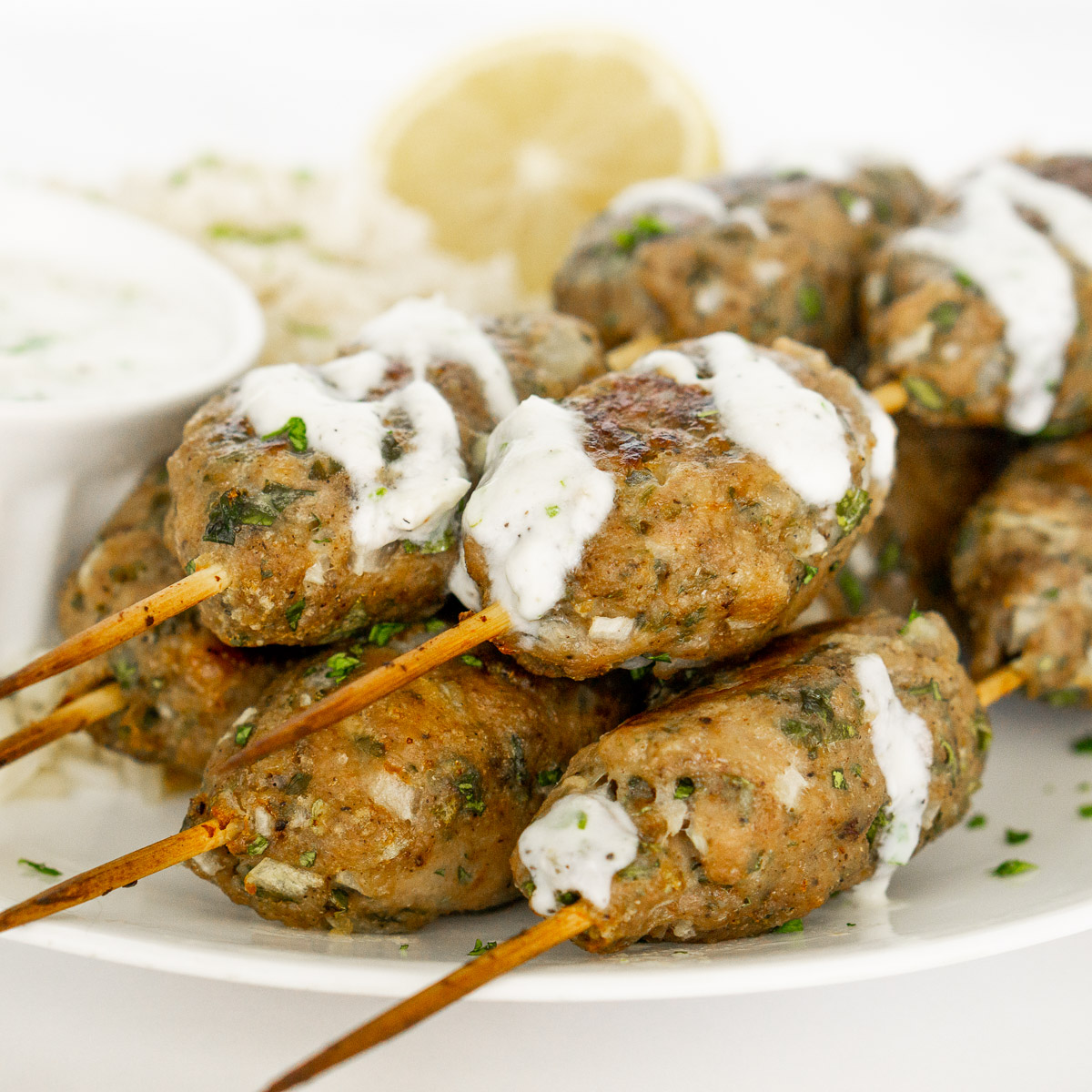 chicken kofta kebabs with yogurt sauce on a plate