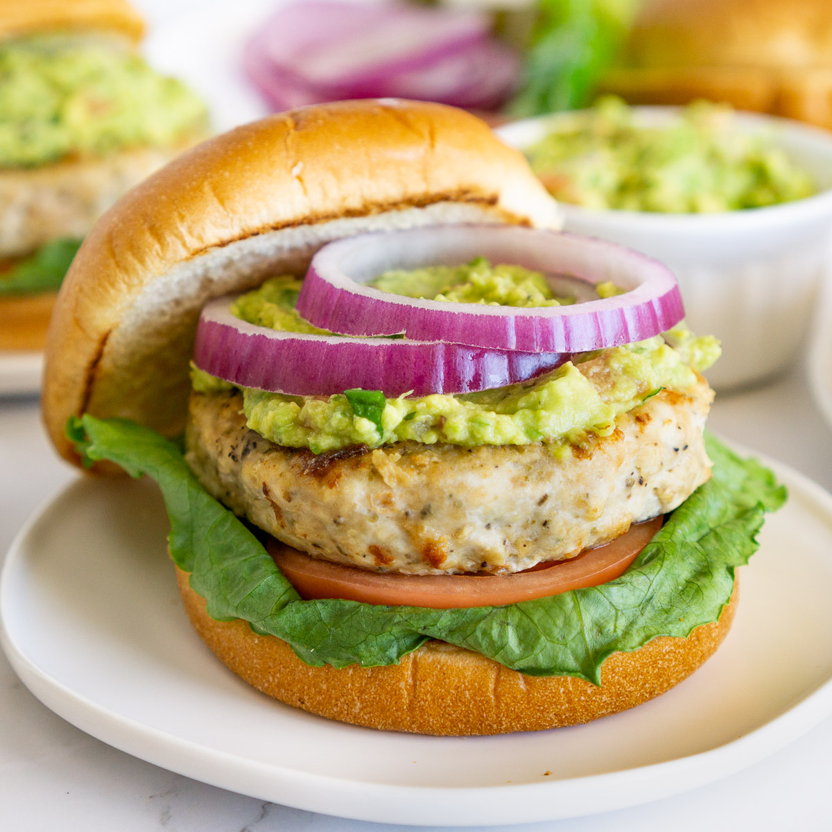 chicken burger with guacamole and red onion