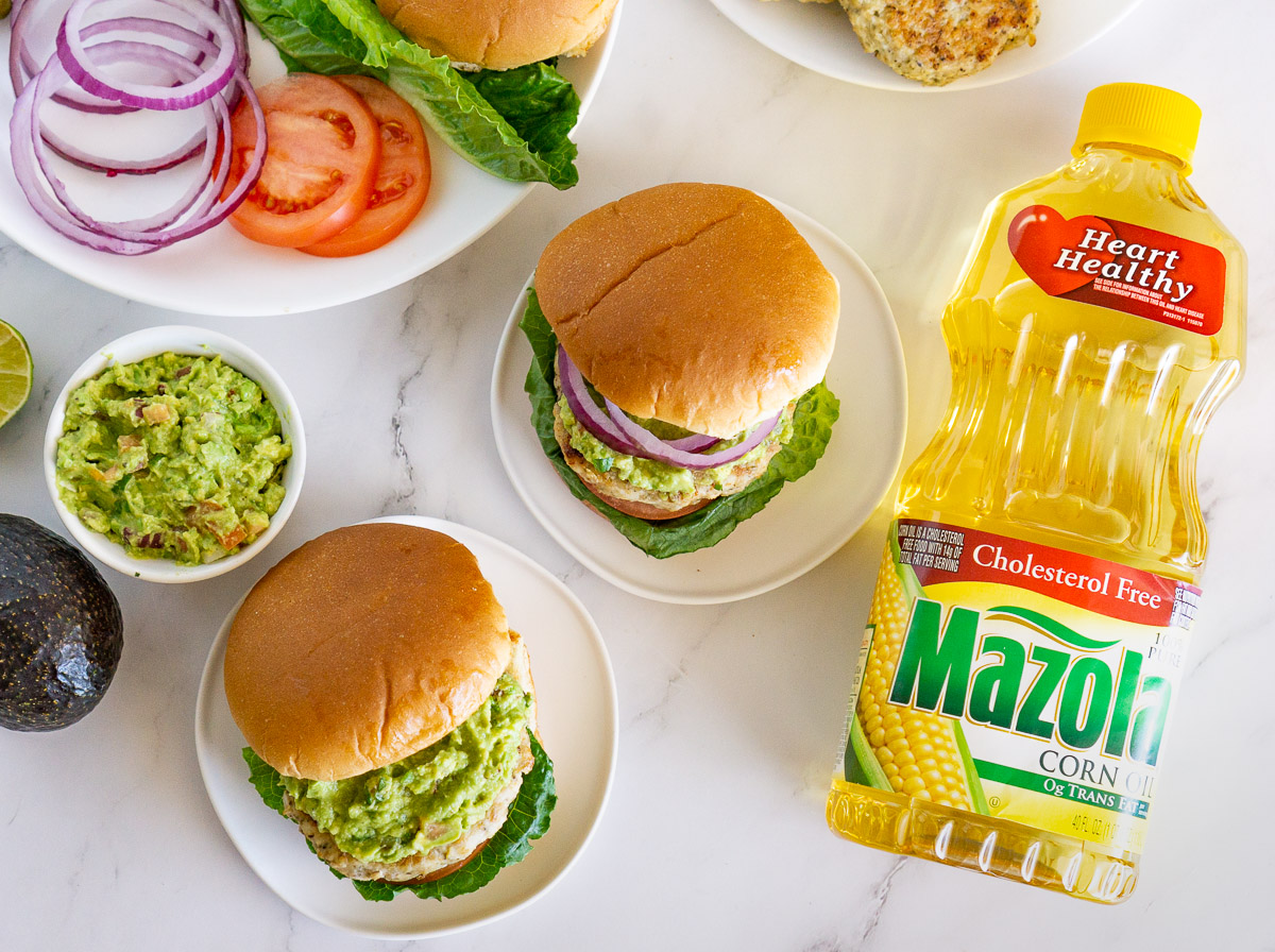 overhead shot of plates with chicken burgers, guacamole, and burger condiments