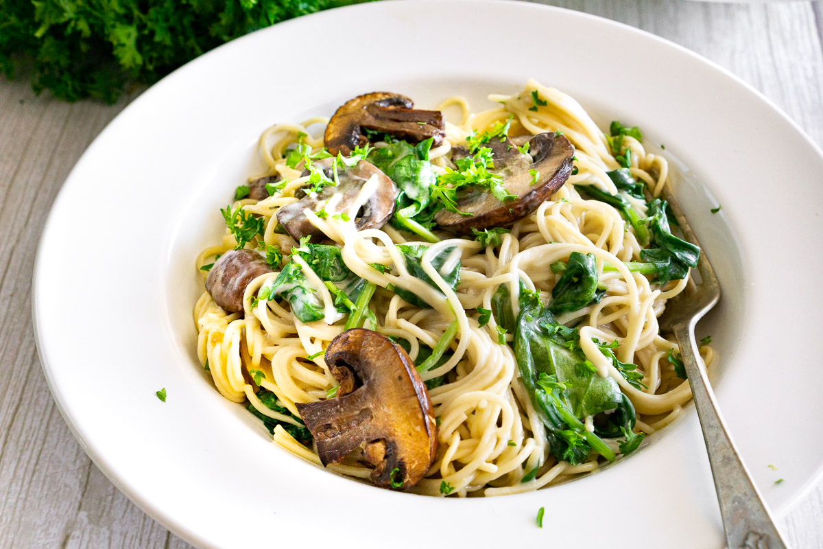 creamy mushroom pasta with spinach in a plate