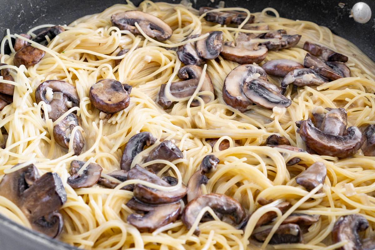 close up picture of angel hair pasta with mushrooms cooked using one pan method