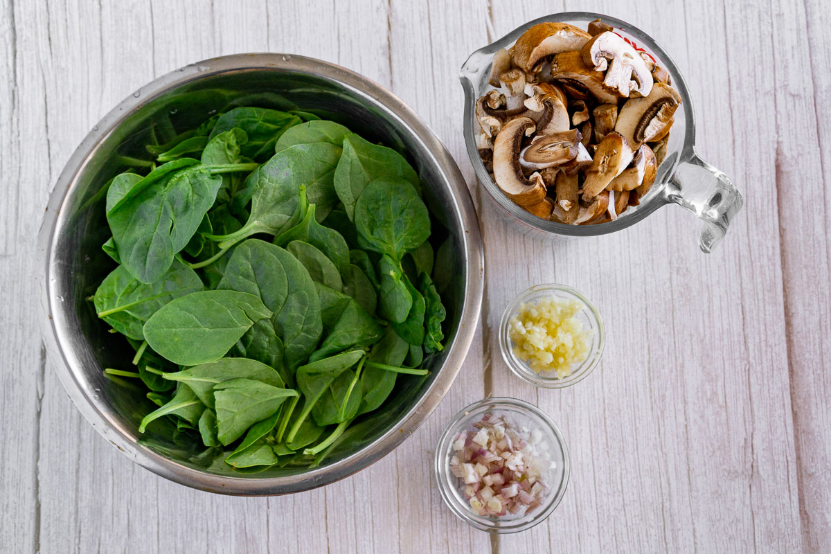 picture of ingredients for one-pot pasta with mushrooms: sliced mushrooms, baby spinach, garlic, shallots