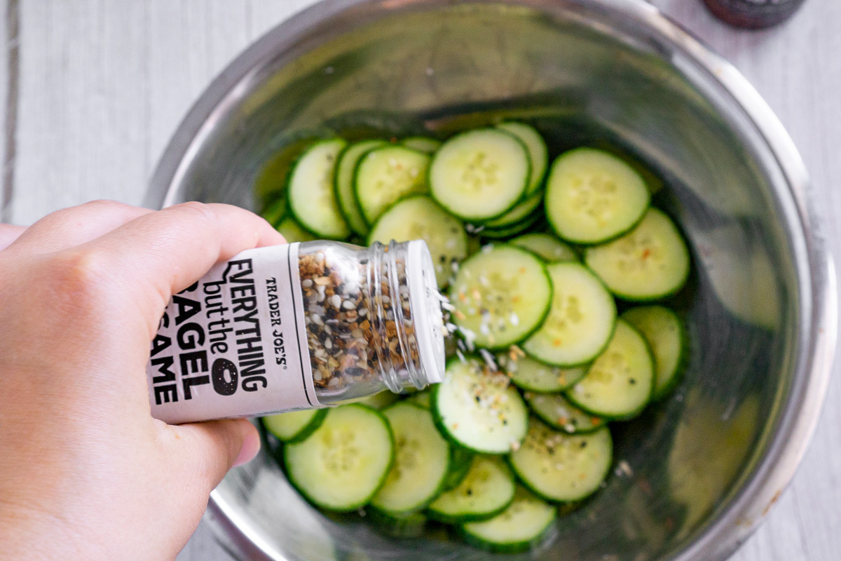 sprinkling everything bagel seasoning on a sliced cucumber salad