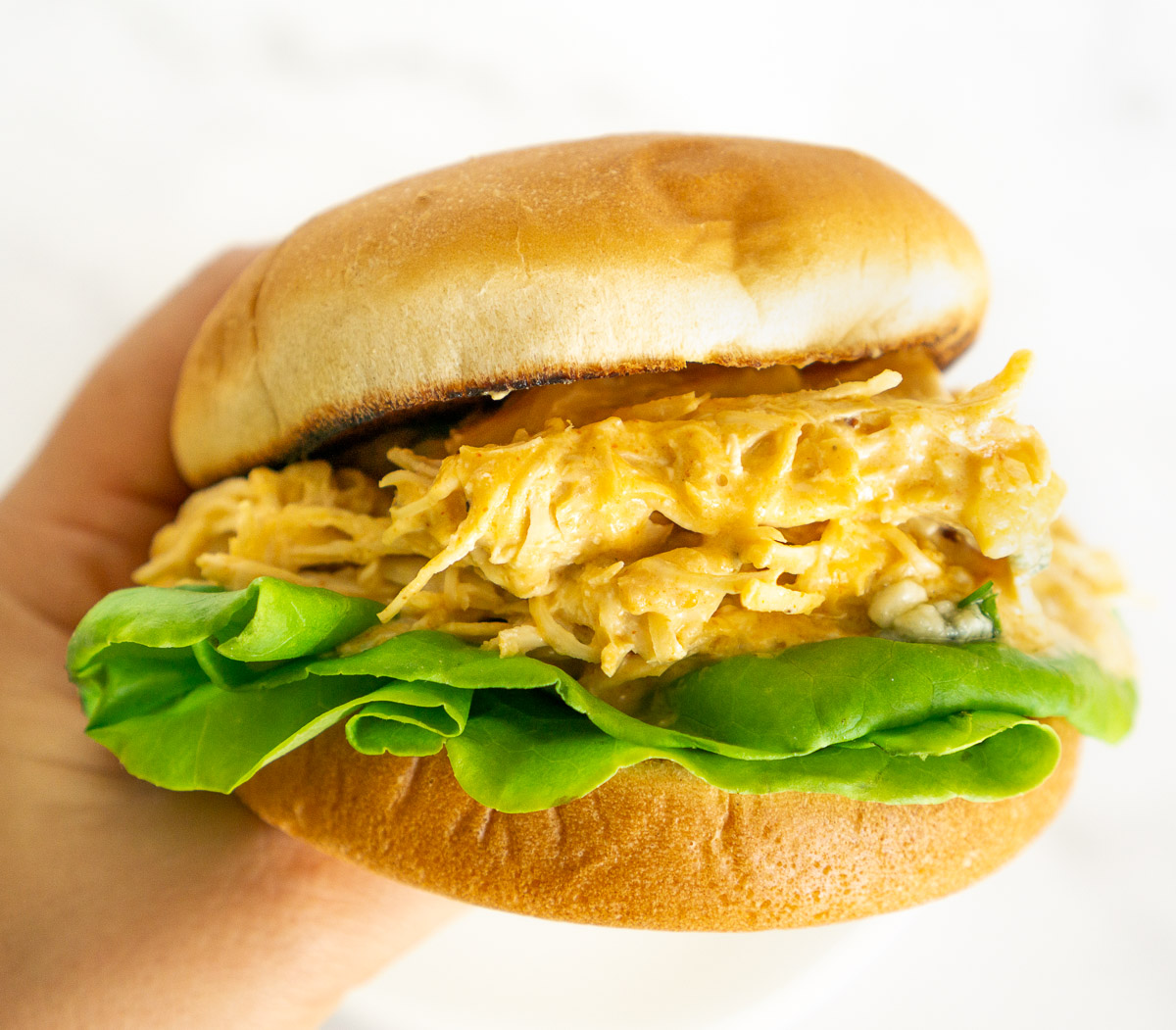 hand holding shredded Buffalo chicken sandwich with lettuce