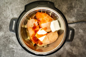 photo of Instant Pot with ingredients for Buffalo chicken inside: chicken, Buffalo sauce, cream cheese, and onions