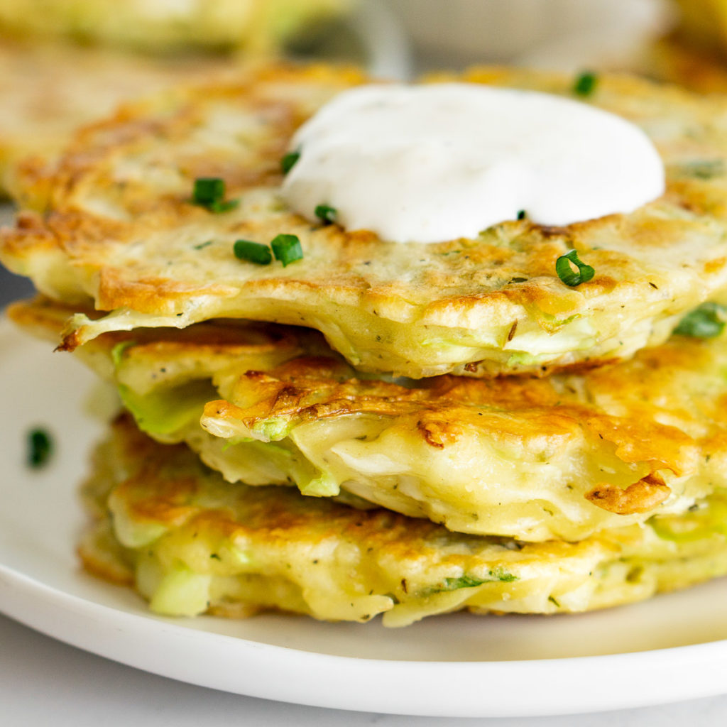 stack of cabbage fritters topped with sour cream sauce