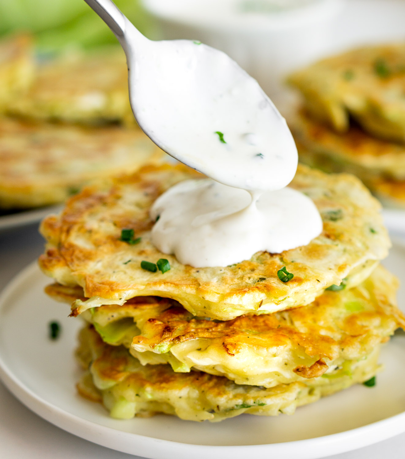 stack of cabbage fritters with sour crema being put on top with a spoon