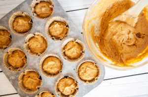 spooning pumpkin muffin batter into the muffin tray