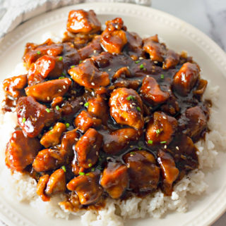 bourbon chicken over a bed of rice on a plate