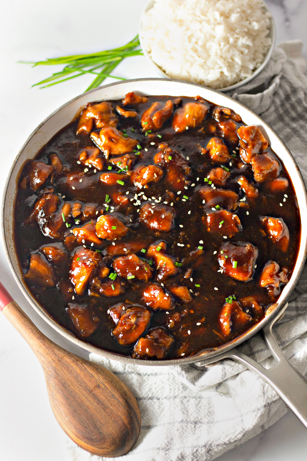 pan of bourbon chicken with a bowl of rice on the side