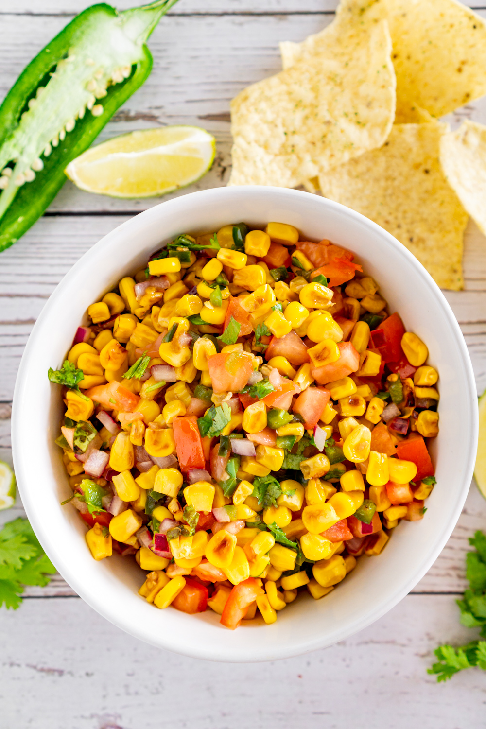 charred corn salad in a bowl surrounded by jalapeno, lime, chips