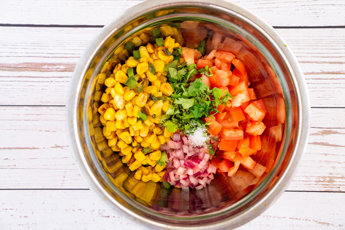 charred corn salad ingredients in a bowl: tomato, red onion, cilantro, charred corn, jalapeno