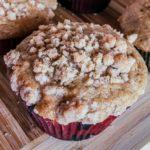 cinnamon coffee cake muffin with crumb topping on a cutting board