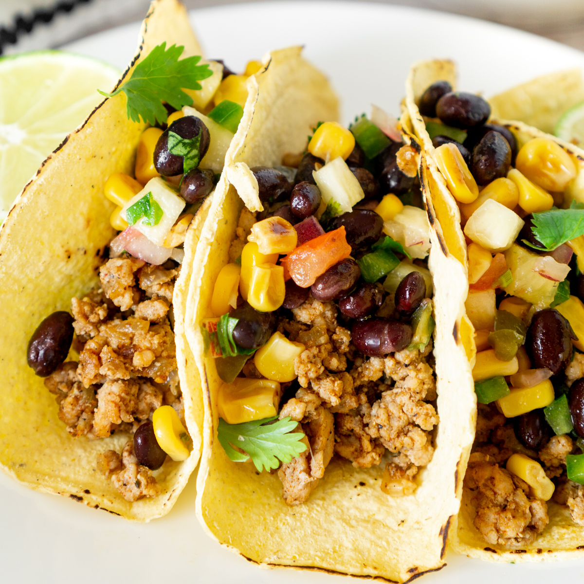 ground pork tacos with pineapple salsa on a plate