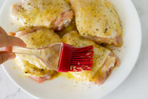 brushing honey mustard sauce onto chicken thighs