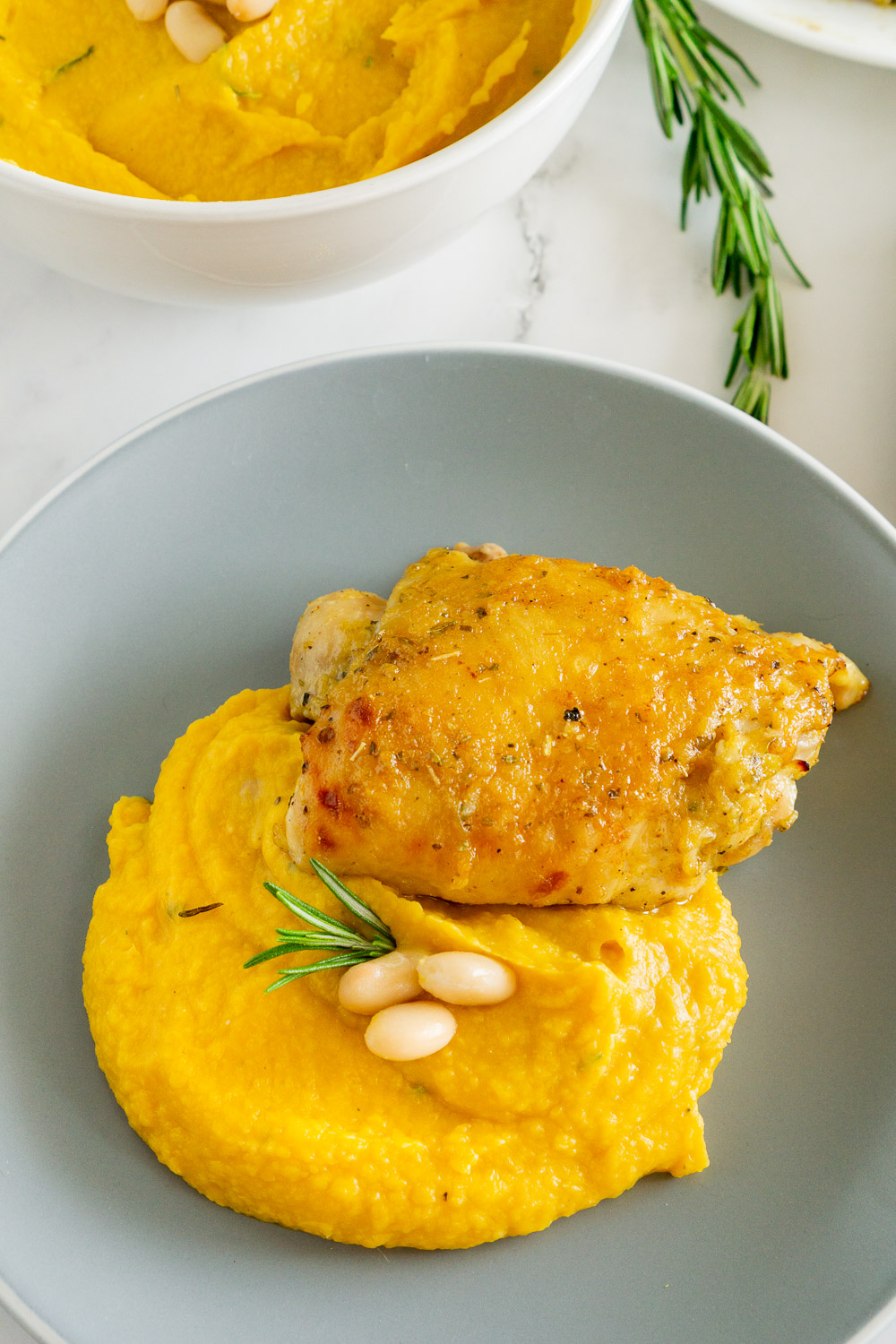 butternut squash mash and white beans on the side of honey roasted chicken thighs