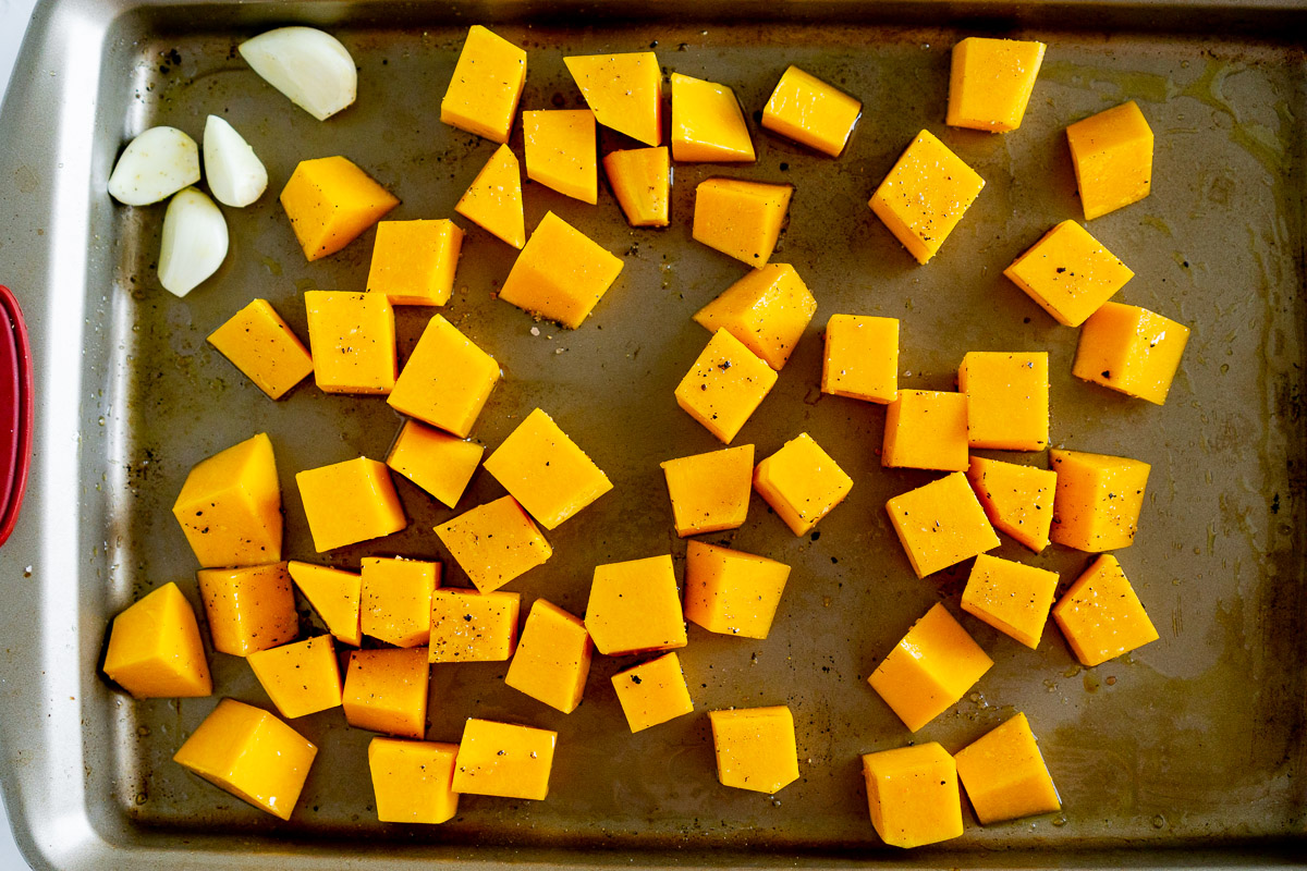 butternut squash and garlic cloves on a roasting pan