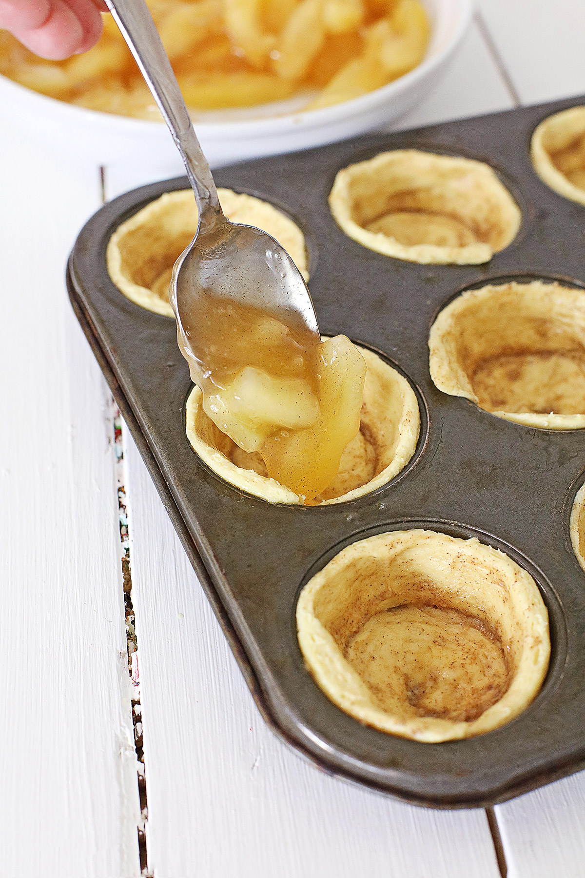 spooning apple pie filling into cinnamon muffin cups