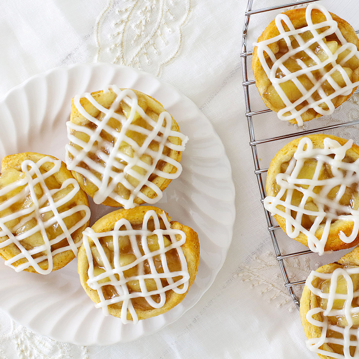 plate of mini apple pie cups and a cooling rack with mini apple pie cups