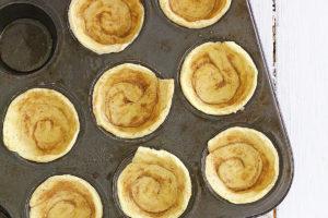 cinnamon rolls pressed into a muffin tin to make a mini cinnamon pie crust