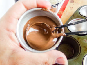 spreading melted chocolate into a hot chocolate bomb mold