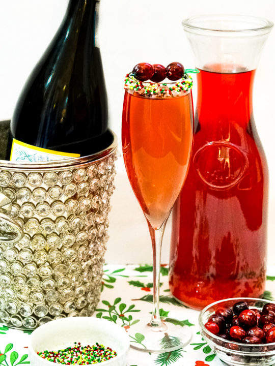 cranberry prosecci drink next to pitcher of cranberry juice