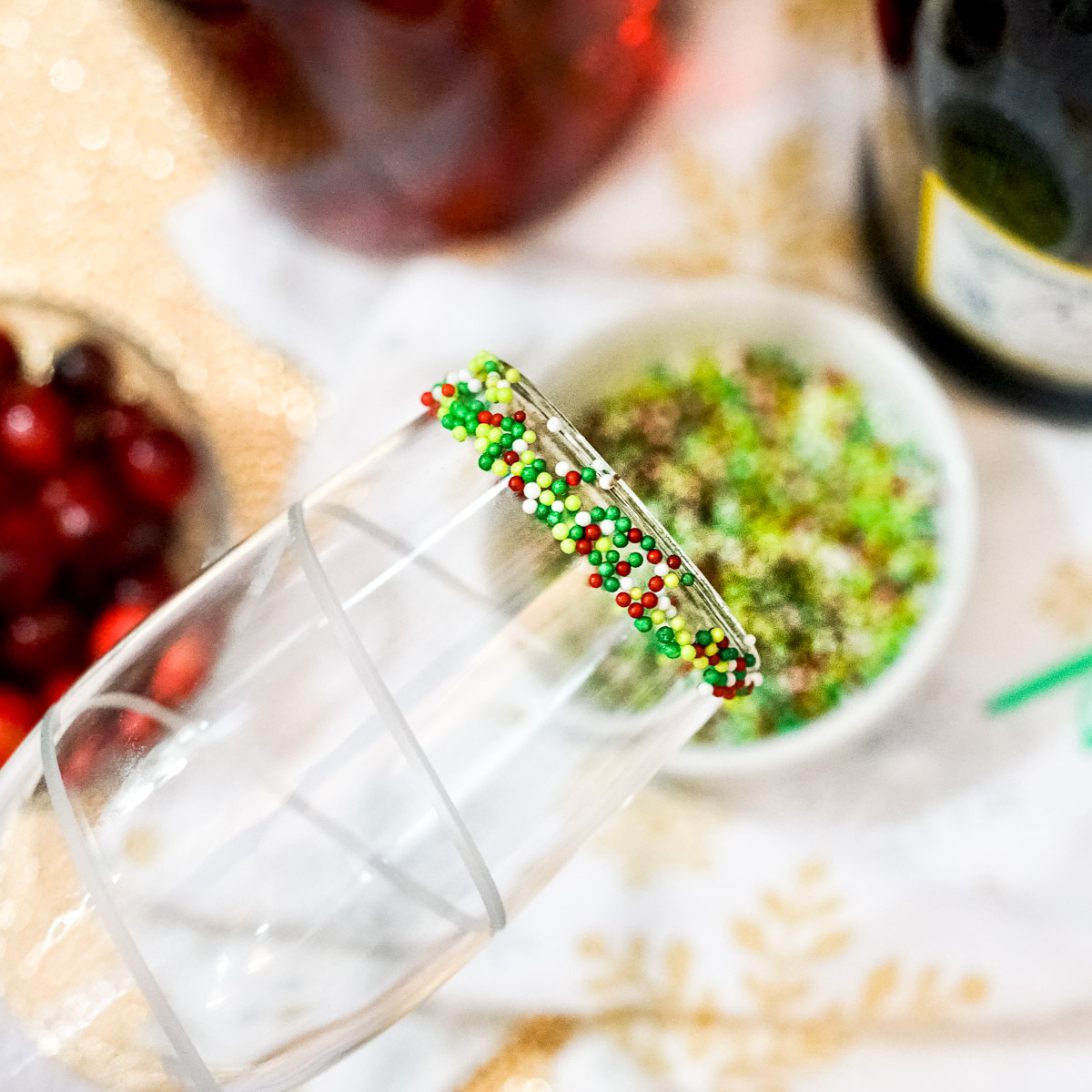adding holiday sprinkles to a champagne glass