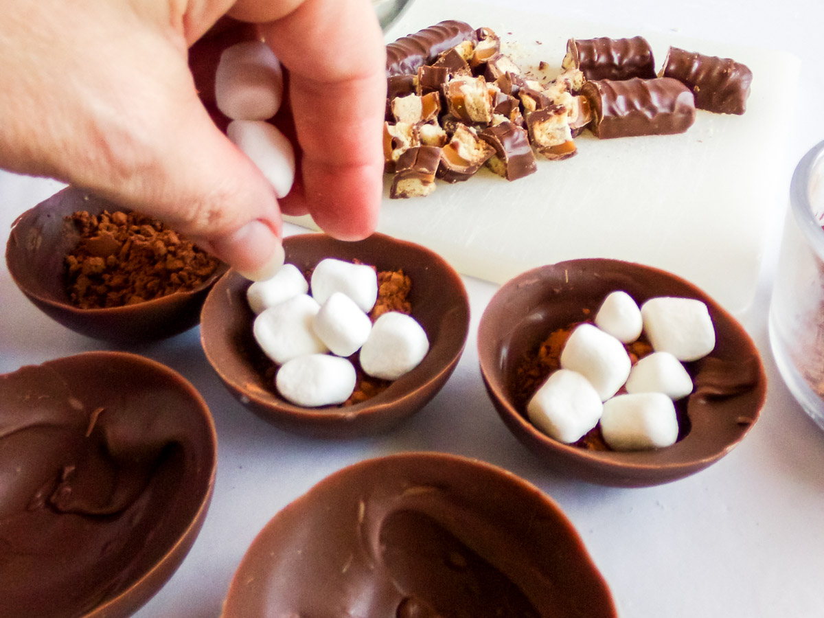 placing hot cocoa and marshmallows into a chocolate candy shell