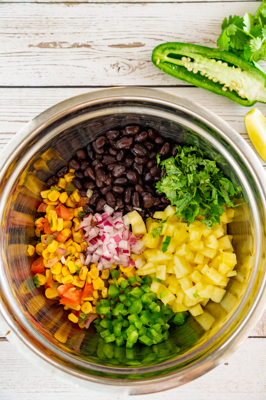 bowl of ingredients to make pineapple black bean salsa: corn, black beans, pineapple, cilantrol, jalapeño, and red onion