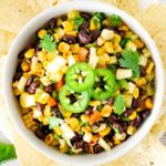 bowl of black bean pineapple salsa with chips on the side